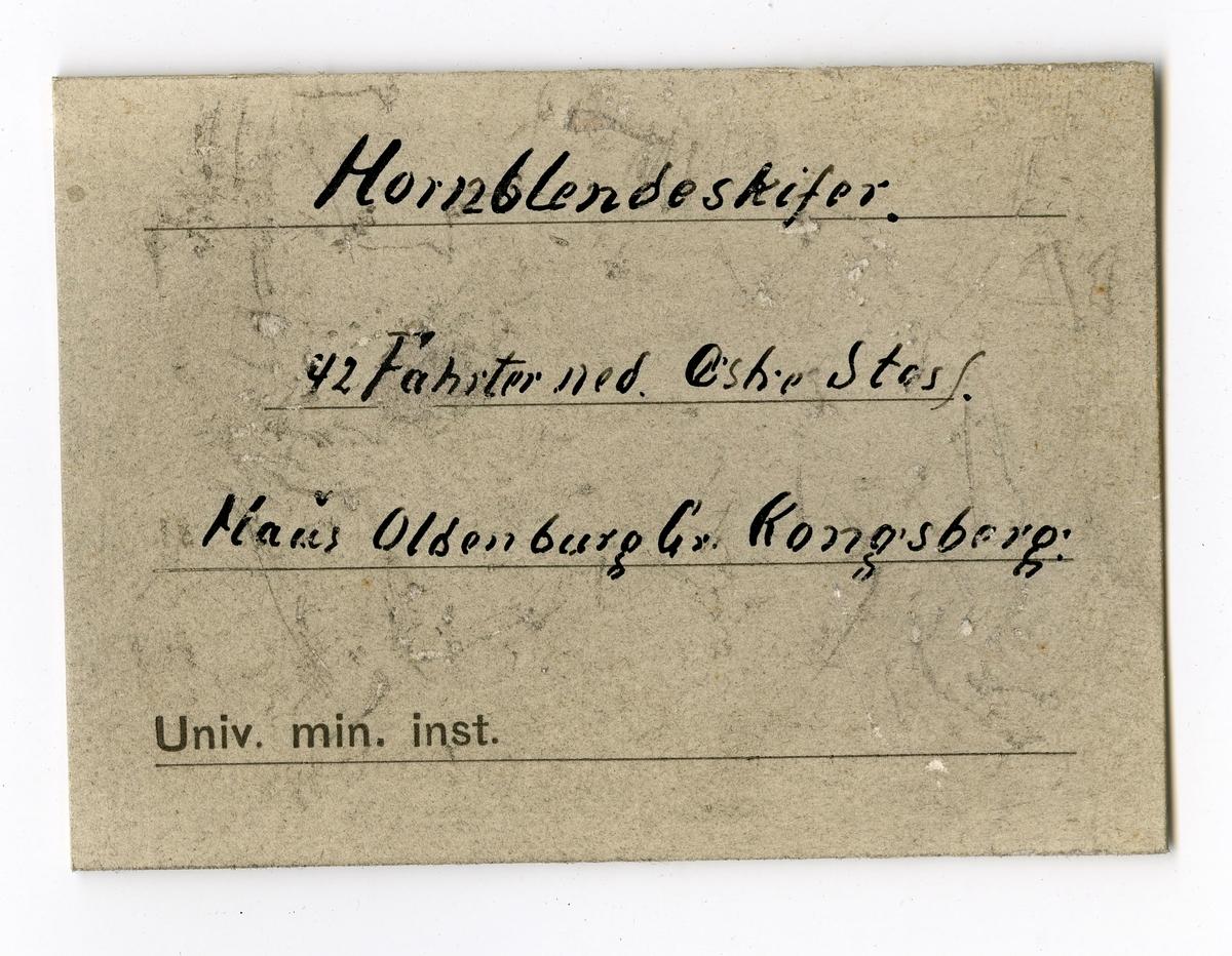 To etiketter i eske:  Etikett 1: Indlagte er fra 42 Fahrter ned tet ved Øststossen   Etikett 2: Hornblendeskifer 42 Fahrter ned. Østre Stoss. Haus Oldenburg Gr. Kongsberg.