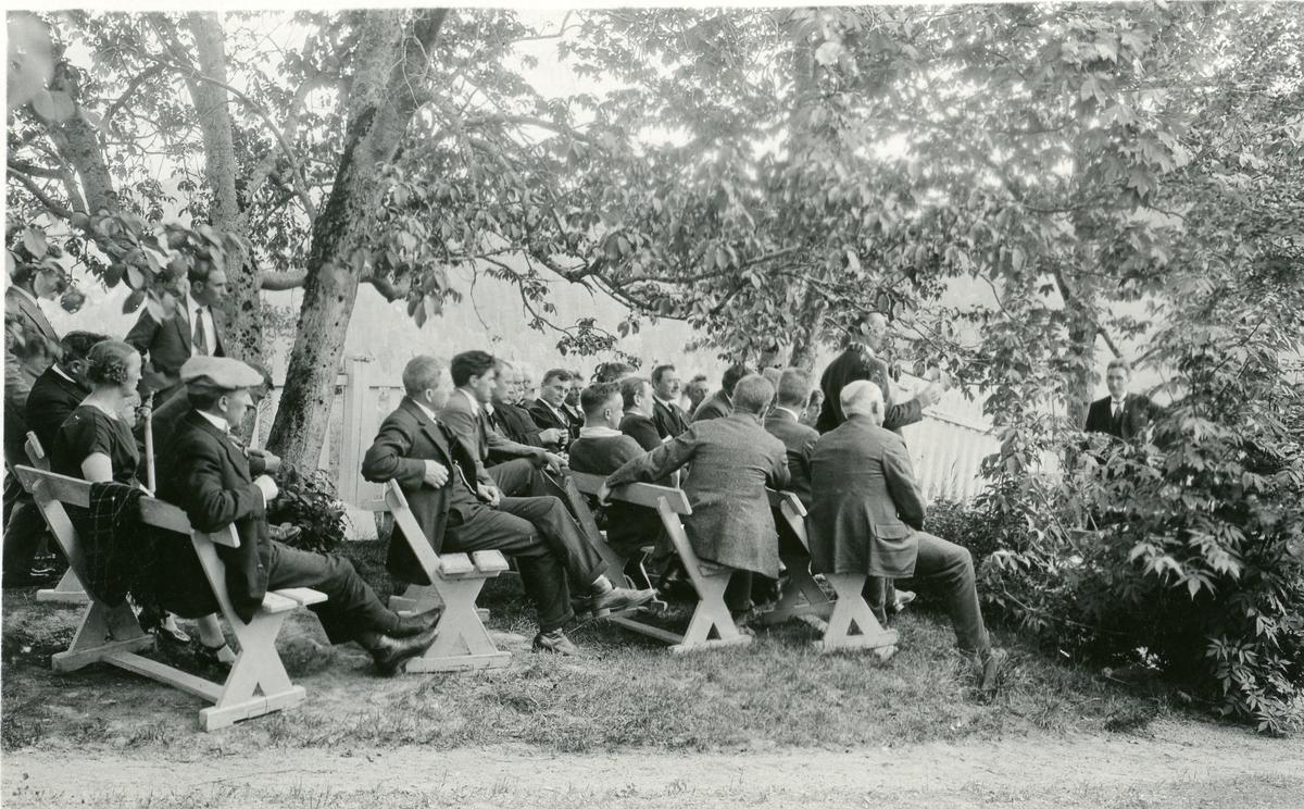 Fra et folkemøte i en park i Amerika. Olaus Islandsmoen taler. Menneskene sitter på trebenker under/ved noen trær.