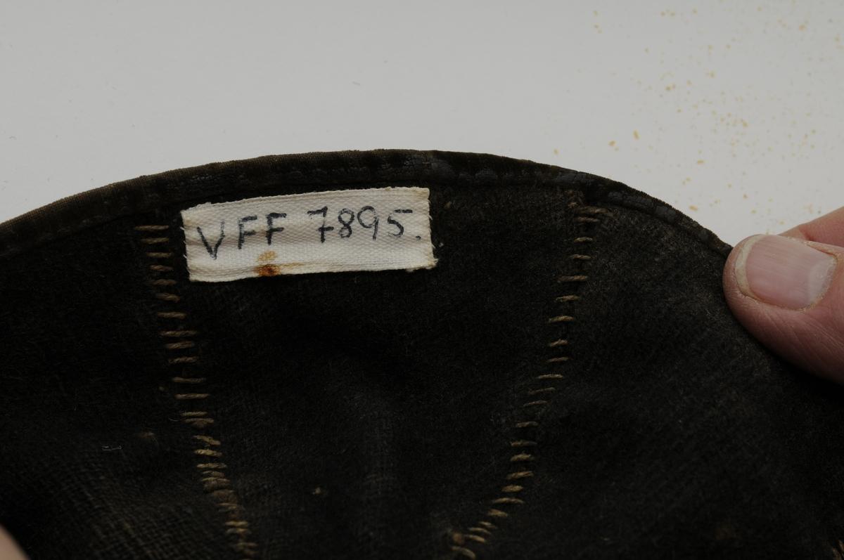 Køllelue i raud ull med svarte fløyelsband oppdelt i åtte seksjonar. To rader med band nederst på lua. Fòra med svart kypertvove ulltøy. Fòret er også delt i åtte seksjonar. Ein runding (2,5 cm) med same ulltøy midt inne i lua.