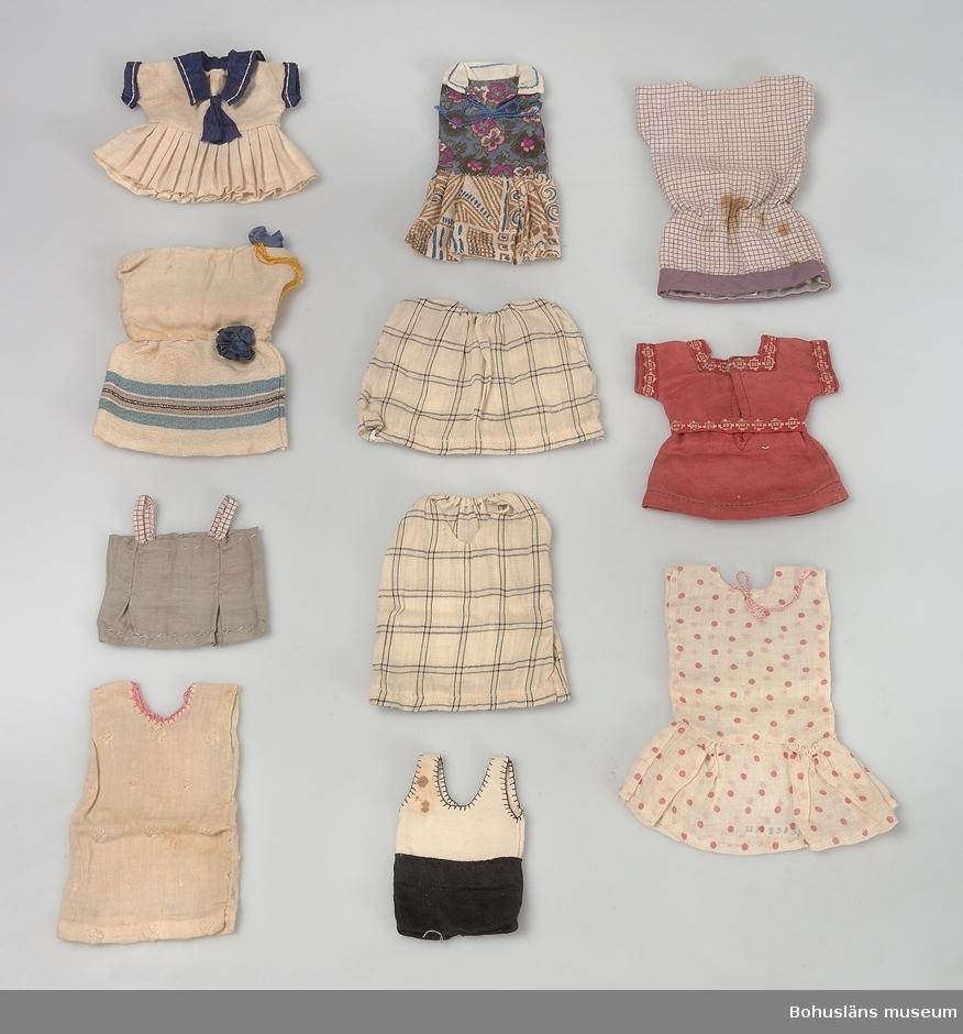 """Beige skolåda med påklistrad etikett varumärke och text: """"Säfsjö Skofabriks AB, Säfsjö Art 11939 läst 95 klack 15 order storl.39 skaft"""" skrivet med blyerts 16-lock. Lådan innehåller 50 st klänningar i olika storlekar och färger, 7 st lekdräkter i olika färger och storlekar, 1 par röd-vit-rutiga underbyxor, 1 st spetsmössa, 1 kofta med mössa, 3 st förkläden, 1 större och två mindre lakan."""