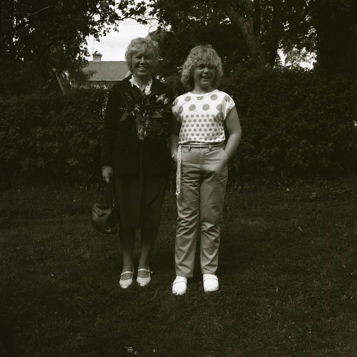 Två kvinnor poserar framför en häck. Den ena bär kjol och kavaj medan den andra bär t-shirt och byxor. En av kvinnorna håller i en stor bukett blommor då bilden är tagen under examensfirande i Alfta kyrka i juni 1983.