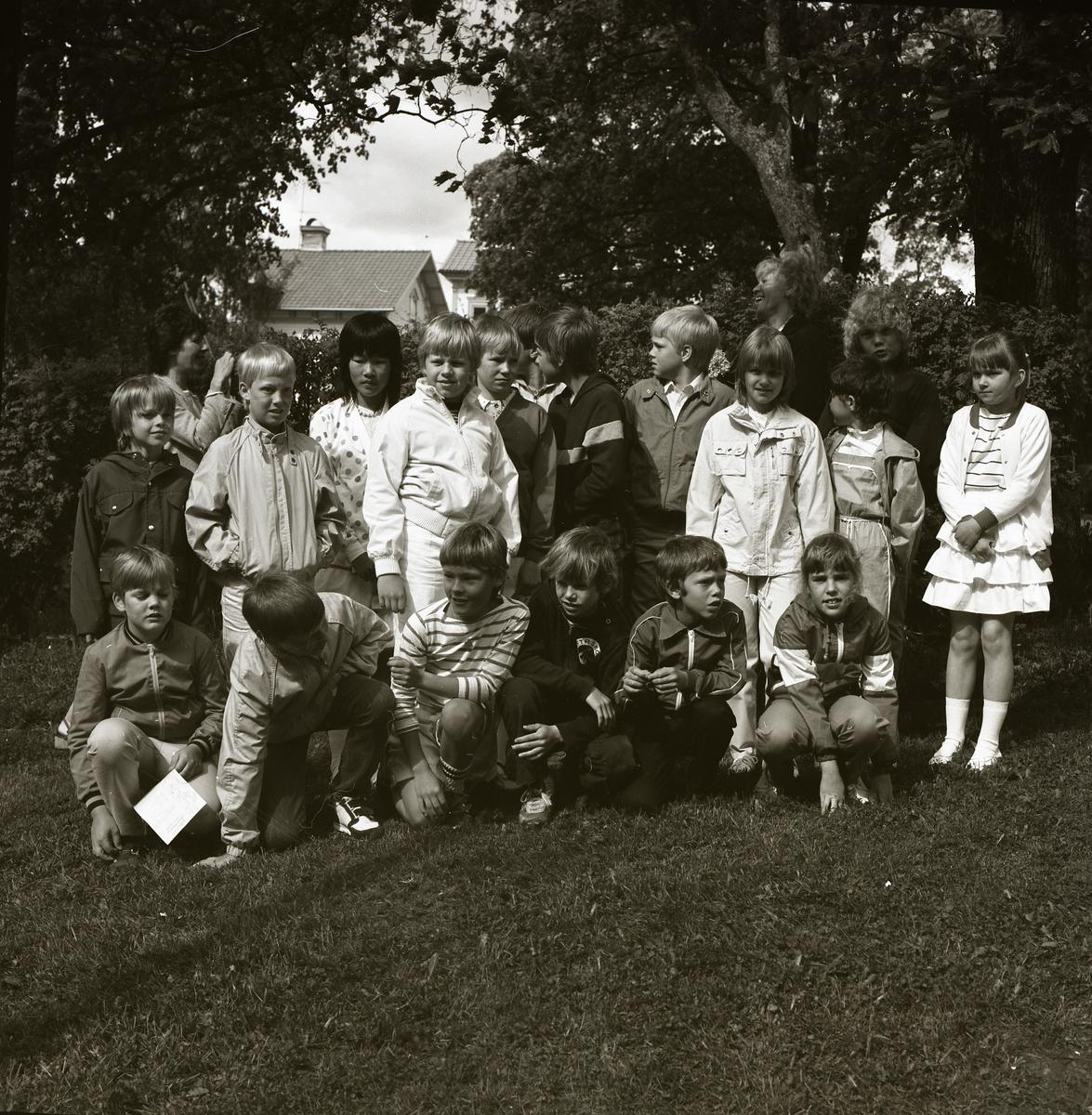 En grupp barn har samlats framför en häck för att ta en gruppfoto. Det är en fin dag i juni 1983 vid Alfta kyrka och barnen är uppklädda. Bakom gruppen skymtar några hustak fram mellan två trädkronor som ramar in motivet.
