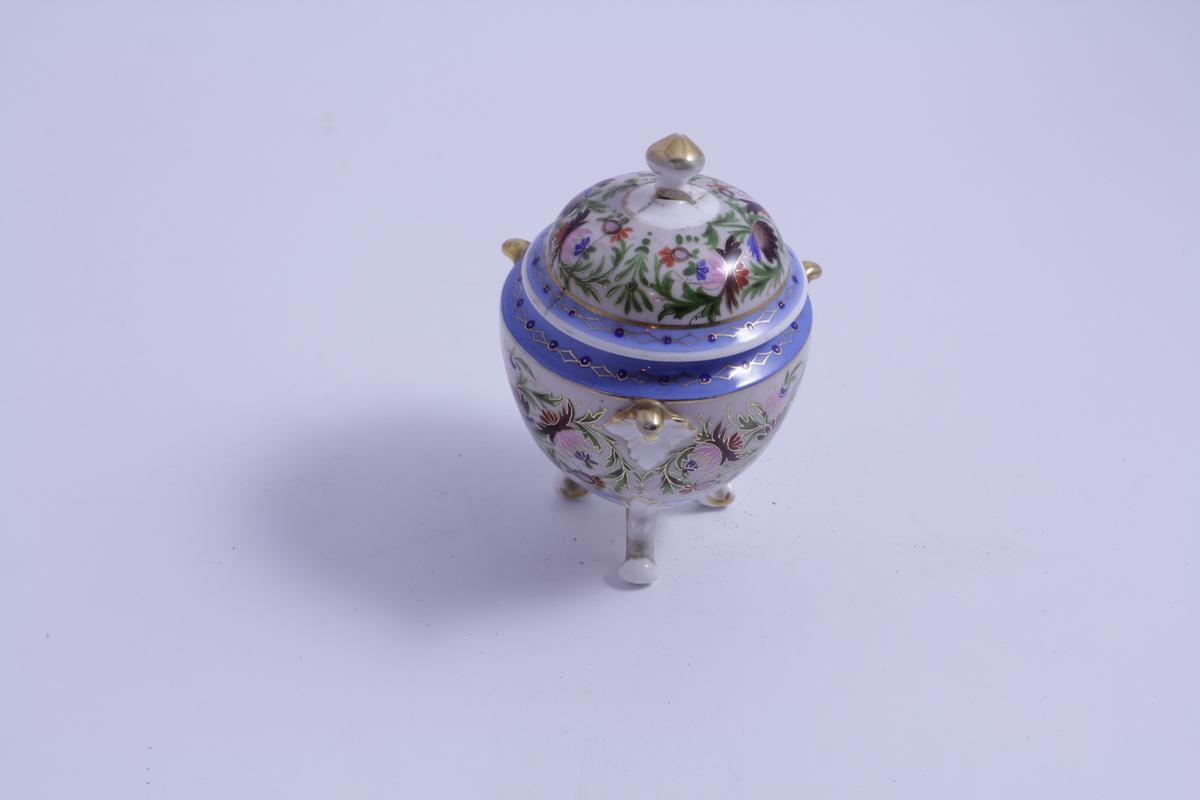 """Dekor: Brede blå bånd rundt korpus og lokk. Gulldekor. Akantusranker og blomster. Soppformet """"tupp"""" under mellom bena og på toppen av lokket (som håndtak). 3 modellerte blad danner små håndtak på korpus."""