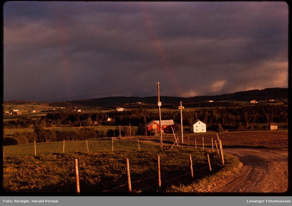 Landskap med regnbuer  og svarte skyer, uvær brygger opp.