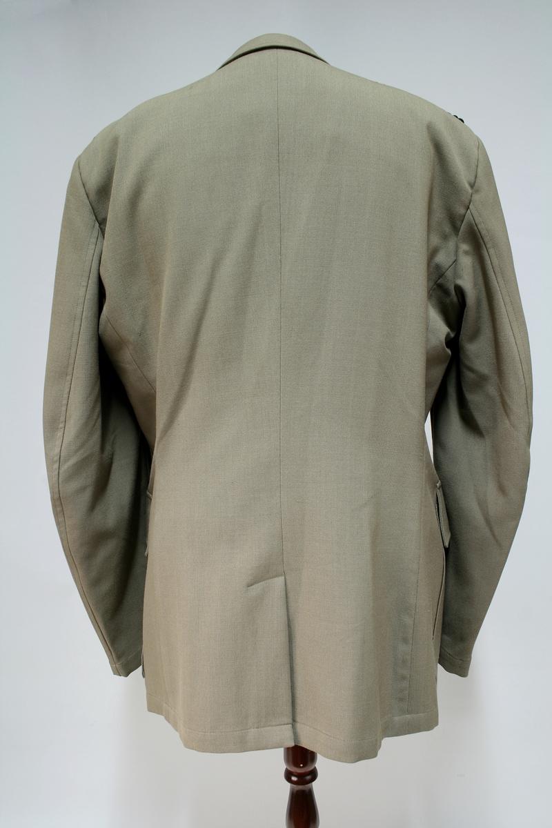Jakken er lik 1953 modellen bortsett fra den rette ryggsømmen.  Khaki jakke med fire knapper, fire ytterlommer, kragespeil med riksløven av metall og skulderklaffer av sorte fletter.