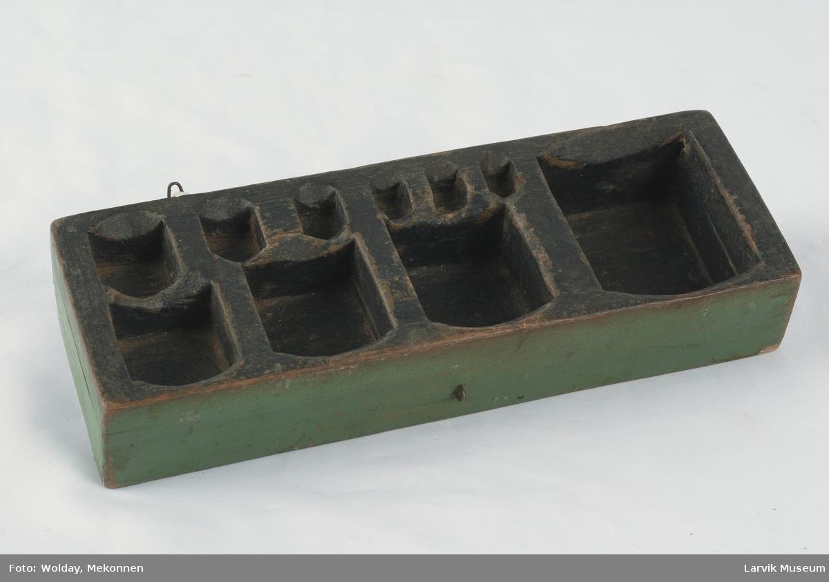 Form: to jernbøyler for feste av lokk. 10 hull av sterkt varierende størrelse til oppbevaring av lodd- ene.