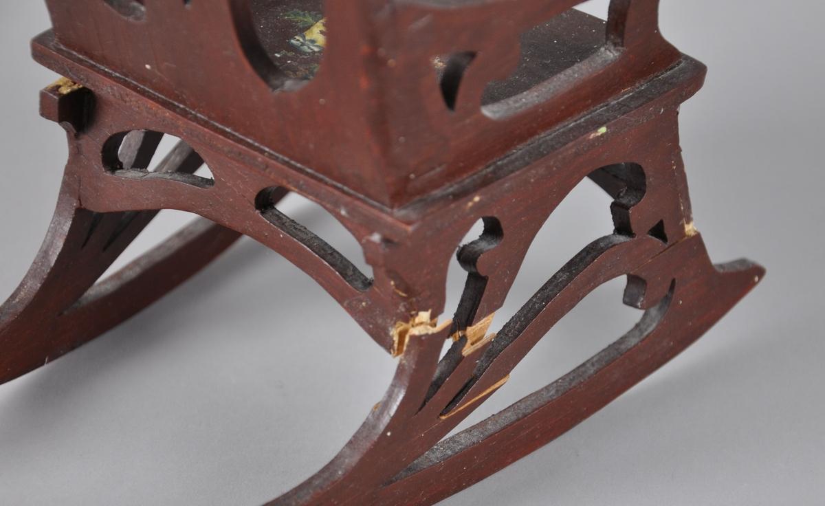 Liten gyngestol av tre. Stolen er malt brun, og ryggstøtte, armstøtter og bein har gjennombrutt, skåret dekor.  På sitteplaten er det malt to fugler i et tre, på ryggstøtten er det to fugler i en krans - begge motivene er avflasset i stor grad. På den ene siden har deler av bein vært knekt av og senere limt på igjen.