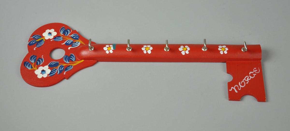 Knaggrekke av tre, formet som nøkkel. Har dekormaling med motiv av hvite blomster og blå bladverk.