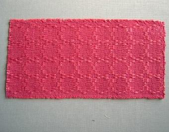 Vävprov, möbeltyg i daldrällsbindning. Mönstret bildar ringar. Varp i mörkt rosa bomullsgarn, nr 16/2. Botteninslag i mörkrosa cottolingarn. Flotterande mönsterinslag i rosa lingarn, 16/1 och 16/2, en tråd av var tillsammans per inslag.