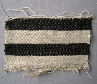 Vävprov, randigt möbeltyg i bomull, och ull vävt i korskypert med inslagseffekt. Distinkt randigt i inslagsriktningen med lika breda ränder i svart och ljust naturgrått. Varp i grått bomullsgarn nr 16/2. Inslag i naturgrått och svart ullgarn; 1-trådigt möbeltygsgarn. Två trådar tillsammans per inslag.