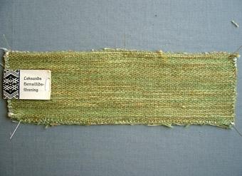 """Vävprov, möbeltyg i bomull, ull och lin vävt i korskypert med inslagseffekt. Melerat i grönt, brunt och gult. Varp i grått bomullsgarn nr 16/2. Inslag i grönt ullgarn; 1-trådigt möbeltygsgarn samt gult och brunt lingarn nr 16/1. Tre trådar tillsammans per inslag; en tråd ullgarn och två trådar lingarn.Märkt med tryckt etikett """"Leksands Hemslöjdsförening"""" och påskriften: """"MÖBELTYG ull/lin BREDD: 132 cm Kr. 460:-""""."""
