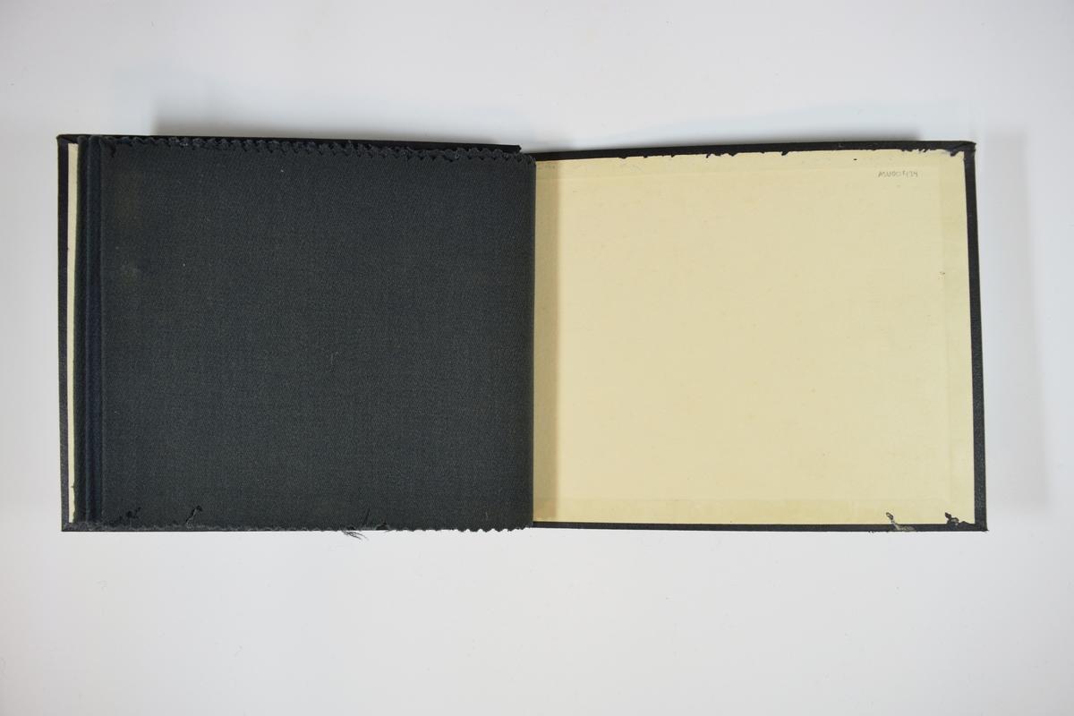 Prøvebok med 3 stoffprøver. Middels tykke stoff med skrå striper i vevmønsteret. Kyperbinding/diagonalvevd. Stoffene ligger brettet dobbelt i boken slik at vranga dekkes. Stoffene er merket med en rund papirlapp, festet til stoffet med metallstift, hvor nummer er påført for hånd. Innskriften på innsiden av forsideomslaget indikerer at alle stoffene i boken har kvalitetsnummer 148.   Stoff nr.: 148/1, 148/2, 148/3.