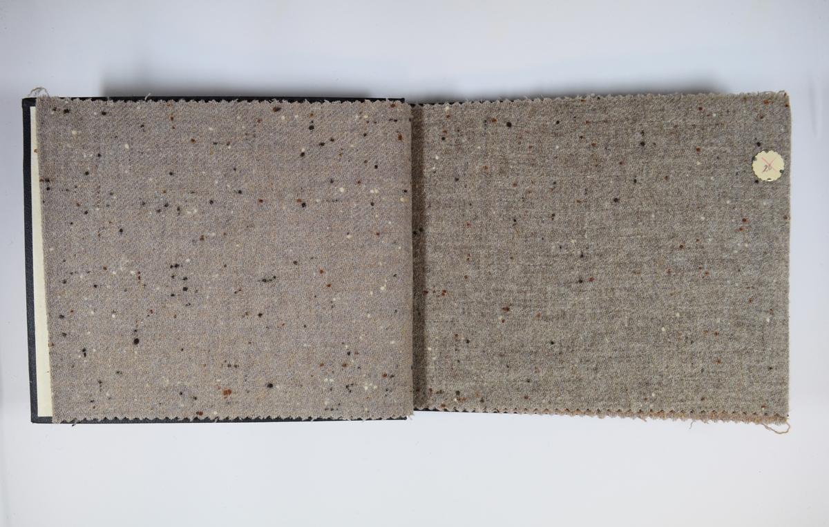 Prøvebok med 6 stoffprøver. Middels tykke stoff med tilsynelatende tilfeldigplasserte prikker. Stoffene ligger brettet dobbelt i boken slik at vranga dekkes. Stoffene er merket med en rund papirlapp, festet til stoffet med metallstift, hvor nummer er påført for hånd. Innskriften på innsiden av forsideomslaget indikerer at alle stoffene har kvalitetsnummer 140.  Stoff nr.: 140/25, 140/26, 140/27, 140/28, 140/29, 140/30.