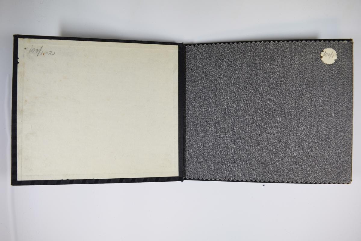 Prøvebok med 2 stoffprøver. Relativt tynne tofargede stoff. Stoffene ligger brettet dobbelt slik at vranga dekkes. Stoffene er merket med en rund papirlapp, festet til stoffet med metallstift, hvor nummer er påført for hånd.   Stoff nr.: 100/1, 100/2.