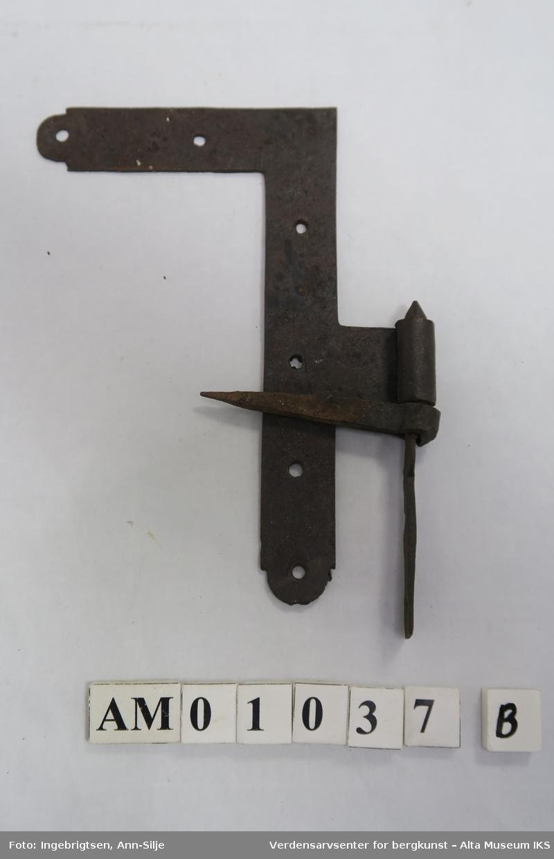 To rettvinklet metallbeslag med hengsler festet i nedre del. Hengslene består av et beslag som smalner inn til en spiss, og en tapp som går igjennom et hull i beslaget. Tappen flater ut i nederste del, hvor det er et hull.
