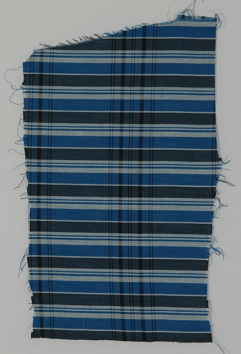 Klänningstyg, 35 x 27 cm, bomull, tuskaft. Rutigt i blått, svart och vitt.  Katalogiserad av Karin Nordenfelt, Elisabet Stavenow, Marie-Louise Wulfcrona-Dagel.