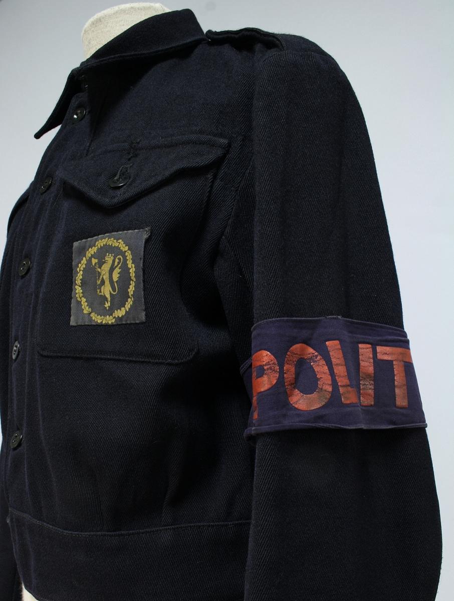 Mørkeblå battledress av den type som benyttes av de britiske A.R.P.Services. På venstre brystlomme et merke som viser den norske løve i sn sirkelrund ekekrans, utført i gult på blå bunn.