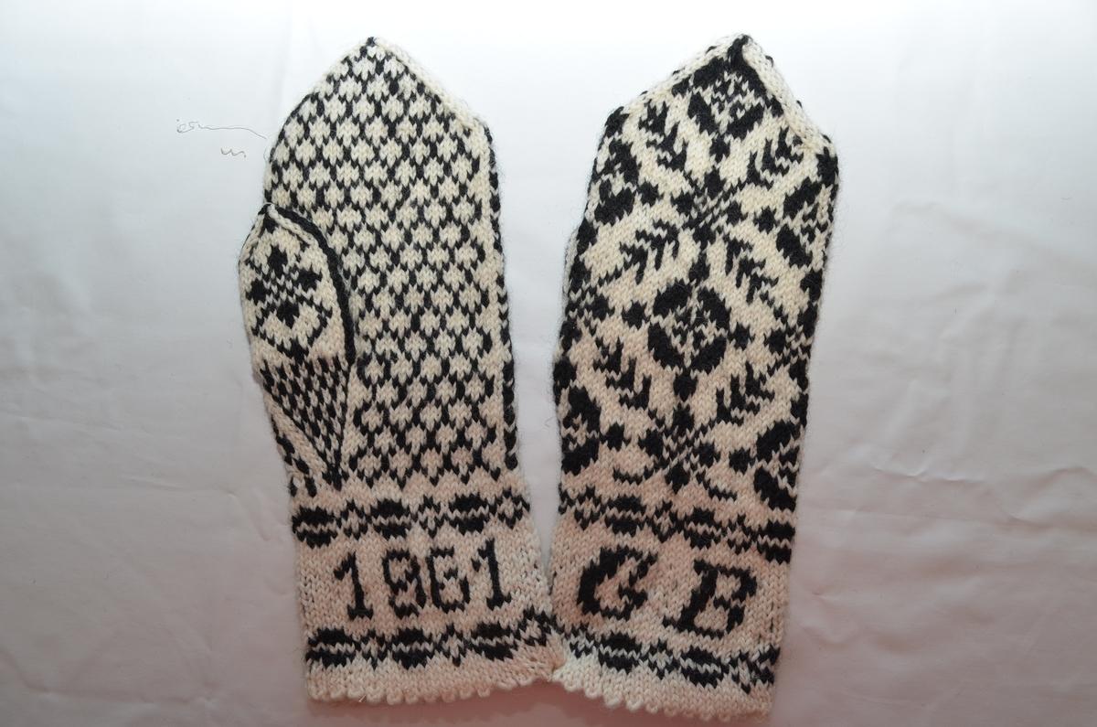 Vott (a+b), rosestrikket i svart og hvitt ullgarn. Bokstavene GB og årstallet 1961 er strikket inn i begge linningene.
