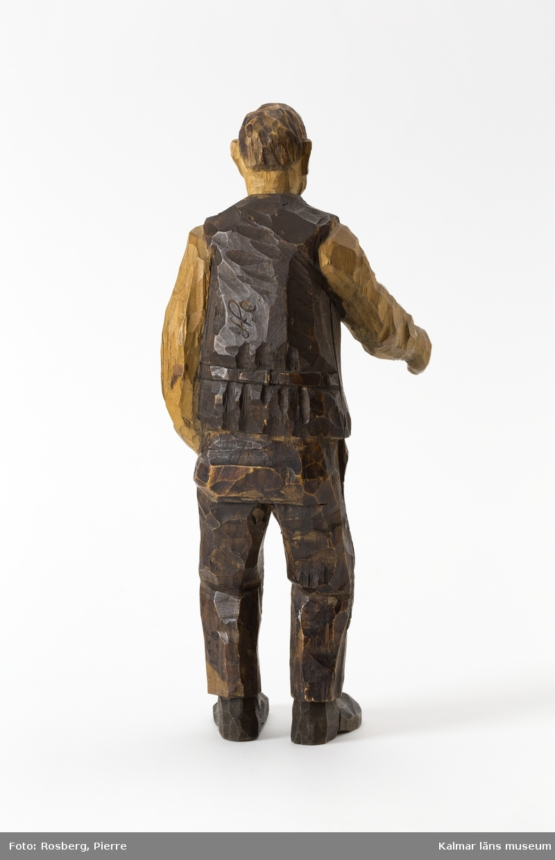 KLM 45932:1 Skulptur, av trä, målad. Figur i form av en stående man. Han har vänster hand i byxfickan och den högra armen sträcker han fram, möjligen har han ursprungligen haft något föremål i den framsträckta handen, barhuvad, klädd i skjorta väst och byxor, stora lappar på knäna, och skor. Signerad på ryggen, H.C., på vänster byxben inskuret, 1926. Målad i bruna nyanser. Tillverkad av Helge Rugland, f. Carlsson.