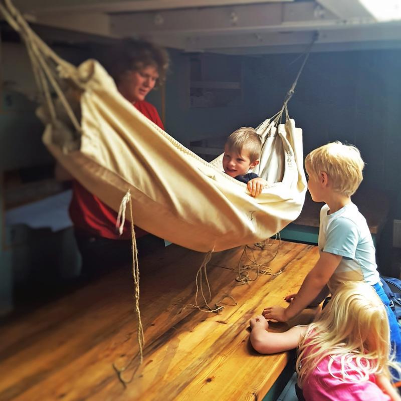 Hengekøye ombord skip, ett barn i hengekøya, to barn utenfor, én voksen bak. (Foto/Photo)