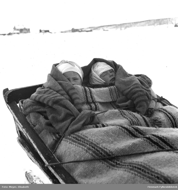 På Sledetur. To barn godt pakket inn i tepper ligger i slede. Det ene teppet er håndvevd i et karakteristsk stripemønster. Fotografert ved påsketider 1940.