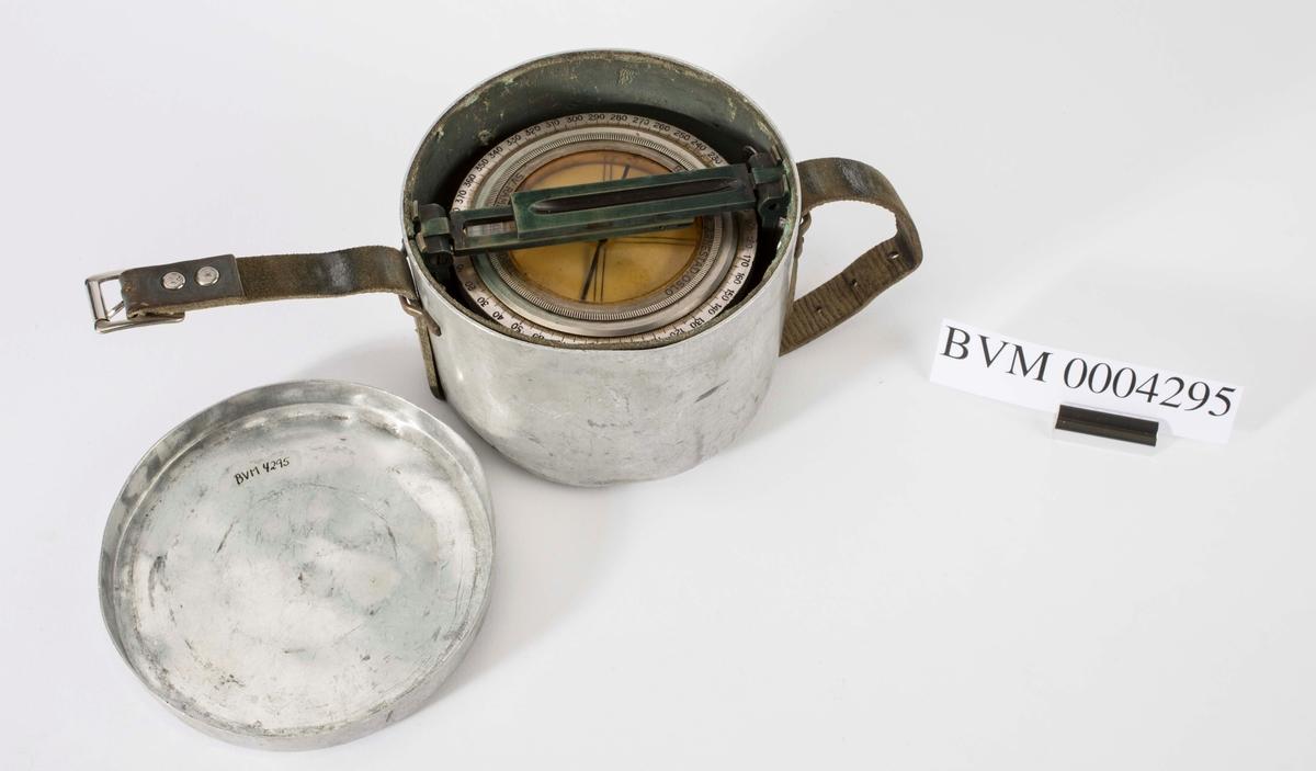 Kompass med 400 graders måleskive. Kompasset ligger inne i en metallboks med festereim i lær. Kompasset er produsert av Bjørnrud & Arnestad, Oslo, etter Sv. Rambergs modell.