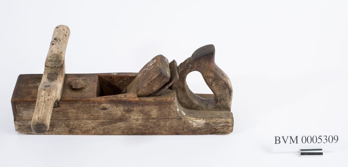 Høvel i tre med to horn/håndtak, kile og dobbelt høveljern. Høvelen har stillingsknapp.
