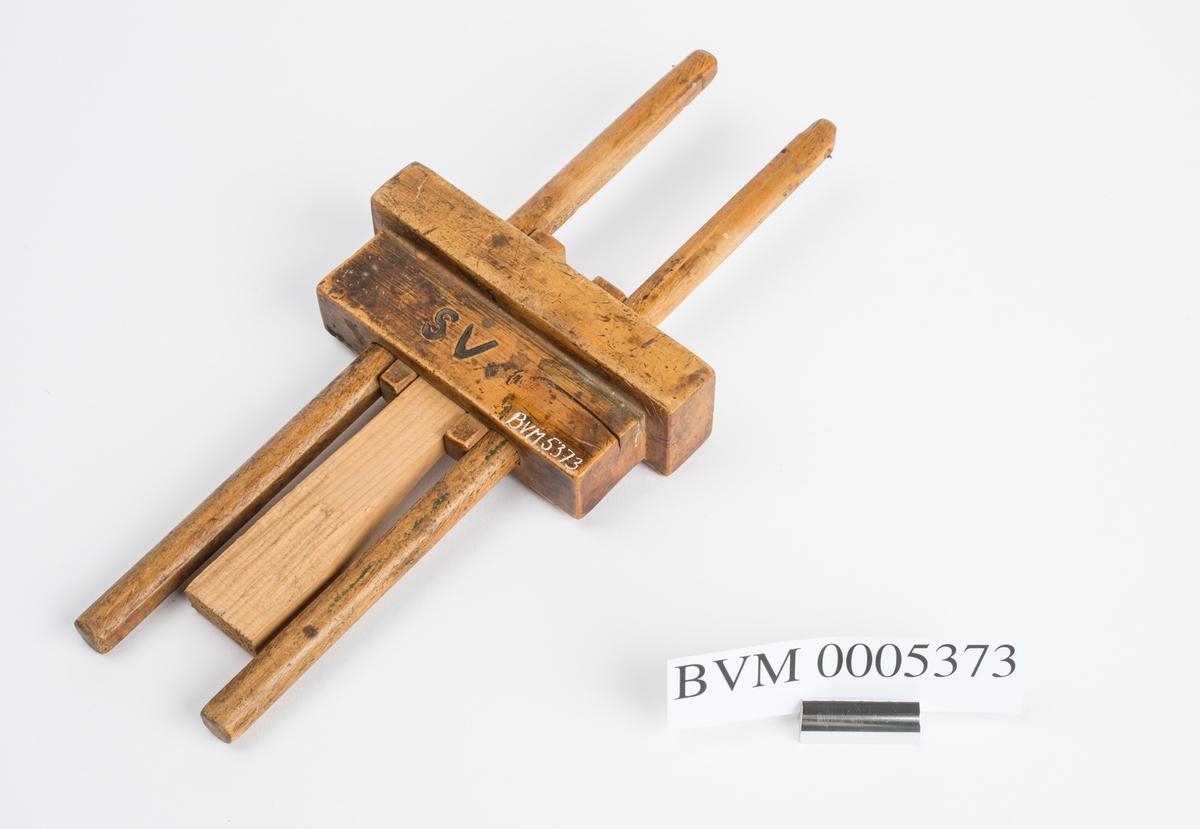 """Strekmålet består av en kloss med to pinner med stift / nål i enden og en kile. Strekmålet ble brukt til å sette av streker på f.eks en planke som skulle splittes. En ønsket avstand ble målt fra stiften på pinnen og ned til klossen. Deretter ble pinnen satt fast med kilen. Klossen ført bortetter planken og stiften satte en strek på denne. På begge sider av klossen er """"SV"""" brent inn."""