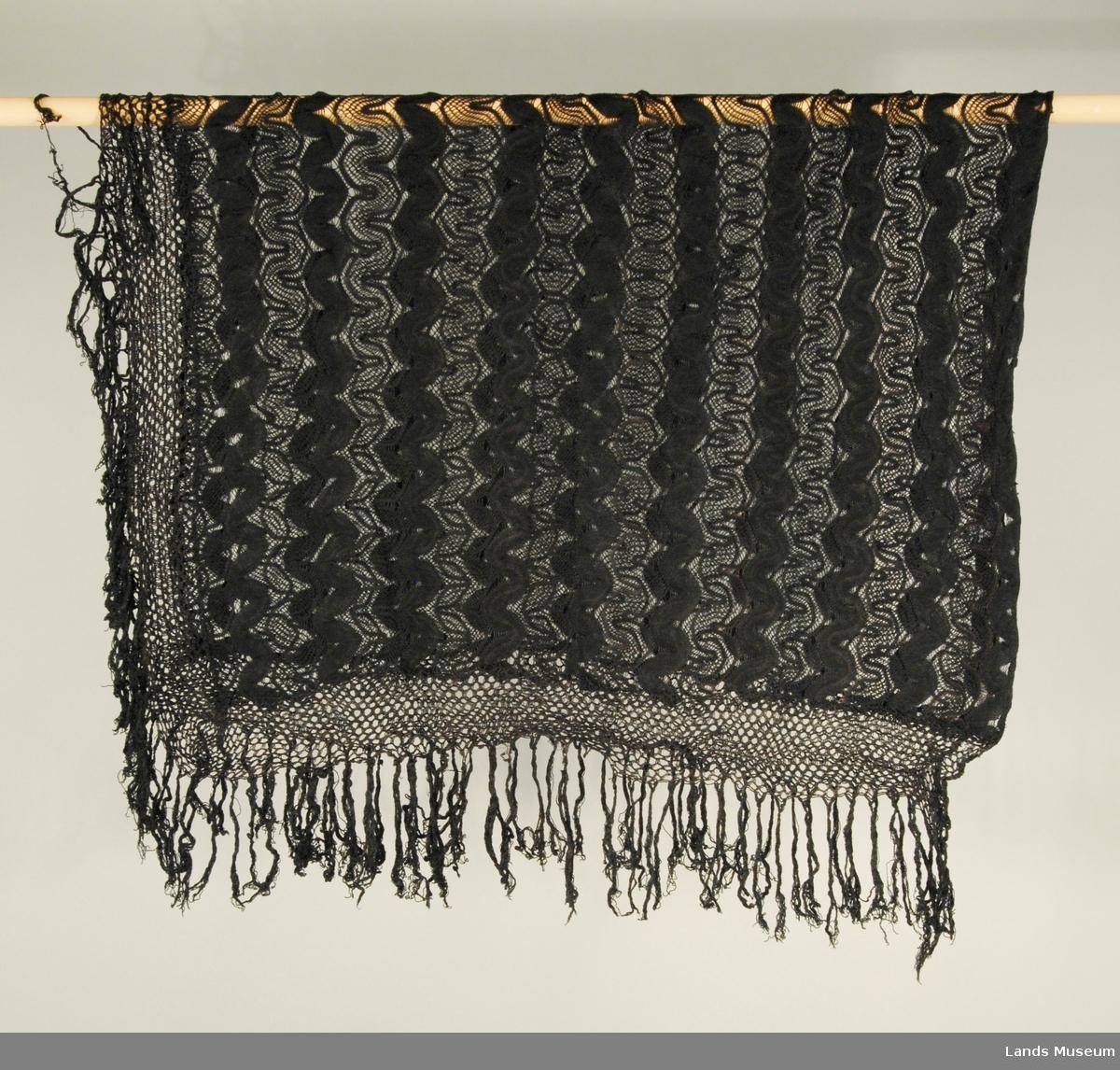 Tricottageprodukt. Bølgeborder av tett glattstrikking og gjennombrutt strikking. Gitterbord med frynser på tre sider.