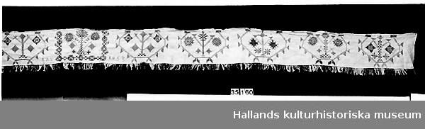 """Broderat hängkläde i hallandssöm med botten i vit linnelärft av tuskaftat väv. Ljusrött (rosa) broderi i elva partier, med ett mittmönster och fem mönsterpartier på var sida (spegelvänt från mitten). Märkt """"AAS"""" vid vänster sida om mittmönstret och """"1853"""" vid höger sida. Sytt av ett tygstycke med stadkant utmed överkanten. Har grov tråckling med lingarn i överkanten som upphängning (original). Påknuten frans av partivis röd och vit bomull längs nederkanten. Monterad mot bomullstyg för upphängning mot träribba.  Frans: 40 mm."""