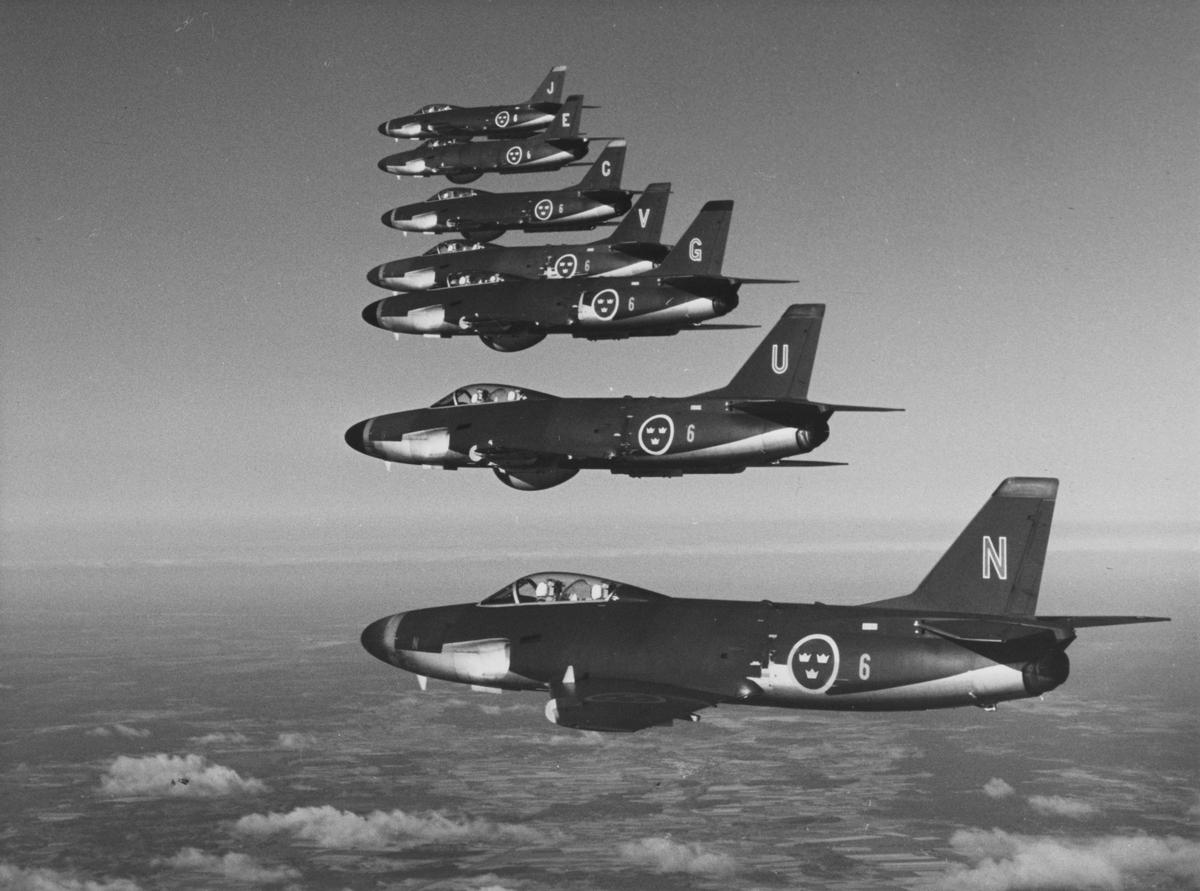 Flygbild av sju stycken flygplan A 32 Lansen från F 6 Västgöta flygflottilj i luften.