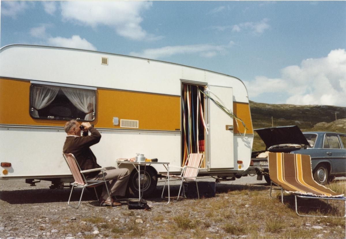 Hans Martin Braate slapper av ved campingvogna, camping stoler, bord og solseng.