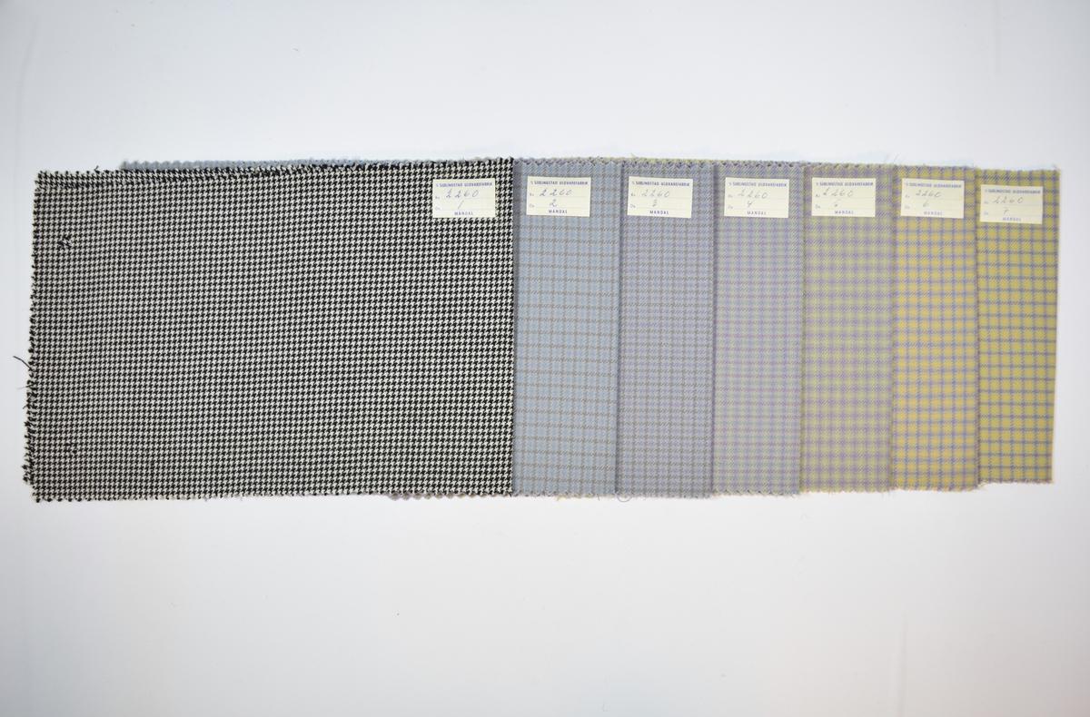 Syv stoffprøver klippet med sikksakk-saks. Relativt tynne stoff med rutemønster eller lignende i ulike farger. Det første stoffet har et annet mønster enn de resterende prøvene, samt annen fargeskala. Kyperbinding/diagonalvevd. Stoffprøvene er brettet på midten slik at formatet passer inn i prøvebøker fra Sjølingstad. Alle stoffene har runde hull etter å ha vært, eller skulle bli, stiftet til en bok eller et hefte. Stoffene er merket med en firkantet papirlapp, limt til stoffet, hvor stoffnummer er fylt ut for hånd i et trykket skjema.   Stoff nr.: 2260/1, 2256/2, 2256/3, 2260/4, 2260/5, 2260/6, 2260/7.