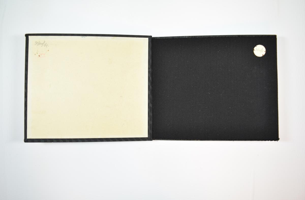 Rektangulær prøvebok med fire stoffprøver og harde permer. Permene er laget av hard kartong og er trukket med sort tynn tekstil. Boken inneholder tynne, men tette, mørke ensfargede stoff med ulike stripemønster. Både kyperbinding og toskaftbinding på noen av stoffene. Det er trolig variasjoner i vevmønsteret boken skal vise. Alle stoffene ligger brettet dobbelt i boken slik at vranga dekkes. Stoffene er merket med en rund papirlapp, festet til stoffet med metallstifter, hvor nummer er påført for hånd.   Stoff nr.: 3400/1, 3400/2, 3400/3, 3400/4.