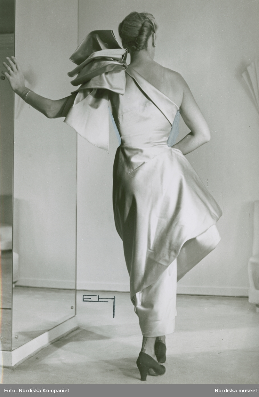 Modell i klänning av Jacques Griffe med stora garneringar på axeln och höften. Håret i en svinrygg.