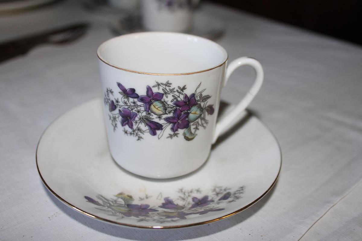Kopp med fat (VF00670b) Vitt porslin med guldkant samt lilafärgade blommönster.