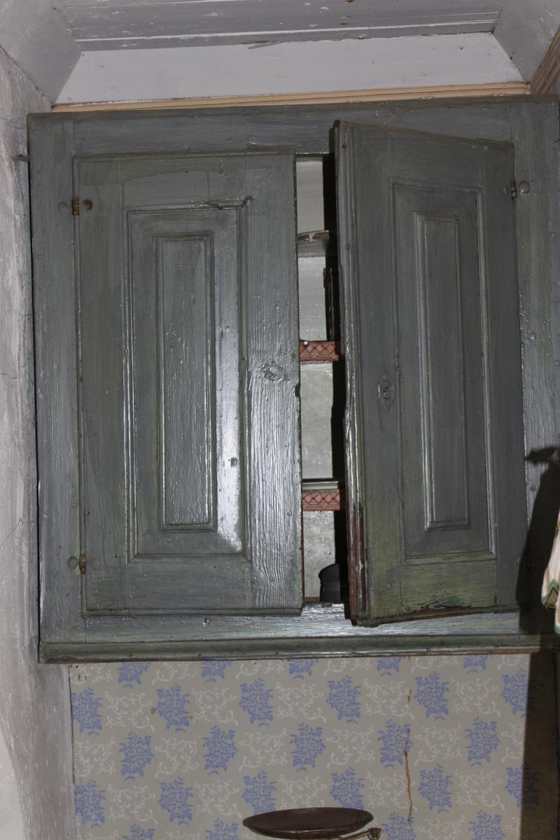 Blågrönt målat vägghängt köksskåp invändigt målat i grått. Tre hyllplan med textila kantband i vitt och rött. Översta hyllplanet är vågformat och har också hack för bestick. Fyra krokar för koppar eller muggar fastsatta under det mittersta hyllplanet. Skåpdörrarna har slät ram med nedsänkta brickor och fyrkantig fyllnad. Hasp på insidan av den vänstra dörren. Ett lås har funnits men tagits bort. Nyckelhålet på framsidan av den högra dörren är igensatt och övermålat.