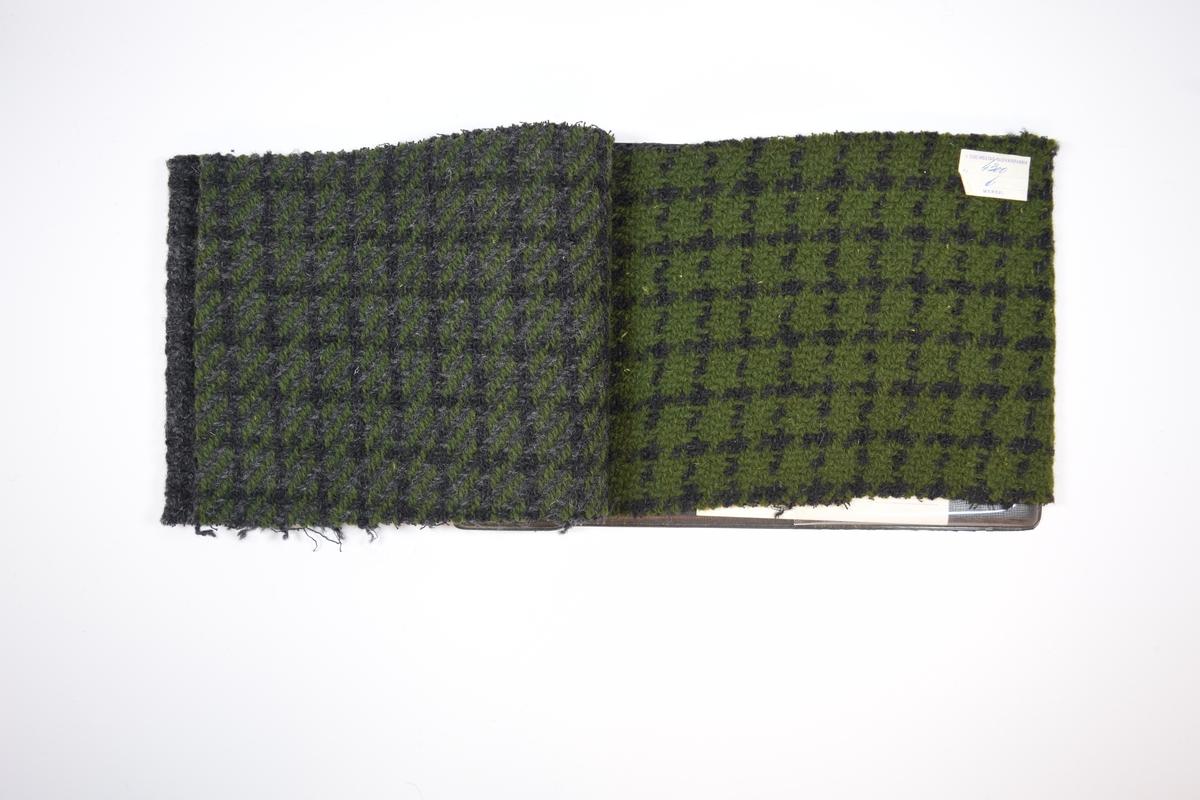 Prøvehefte med 3 prøver. Middels tykke stoff med ruter, ett også med skrå striper. Kyperbinding med tykk ulltråd på forsiden, toskaftbinding med tynnere tråd av bomull eller lignende på baksiden. Stoffene ligger brettet dobbelt i heftet, slik at vranga dekkes. Stoffene er merket med en firkantet papirlapp limt til stoffet, hvor nummer er påført for hånd i et trykket skjema. Heftet har stiv bakplate, trolig av papp, trukket med plast, og samme type plate på forsiden der heftet er stiftet som dekker ca. 5 cm av forsiden.    Stoff nr.: 4300/4, 4300/5, 4300/6.