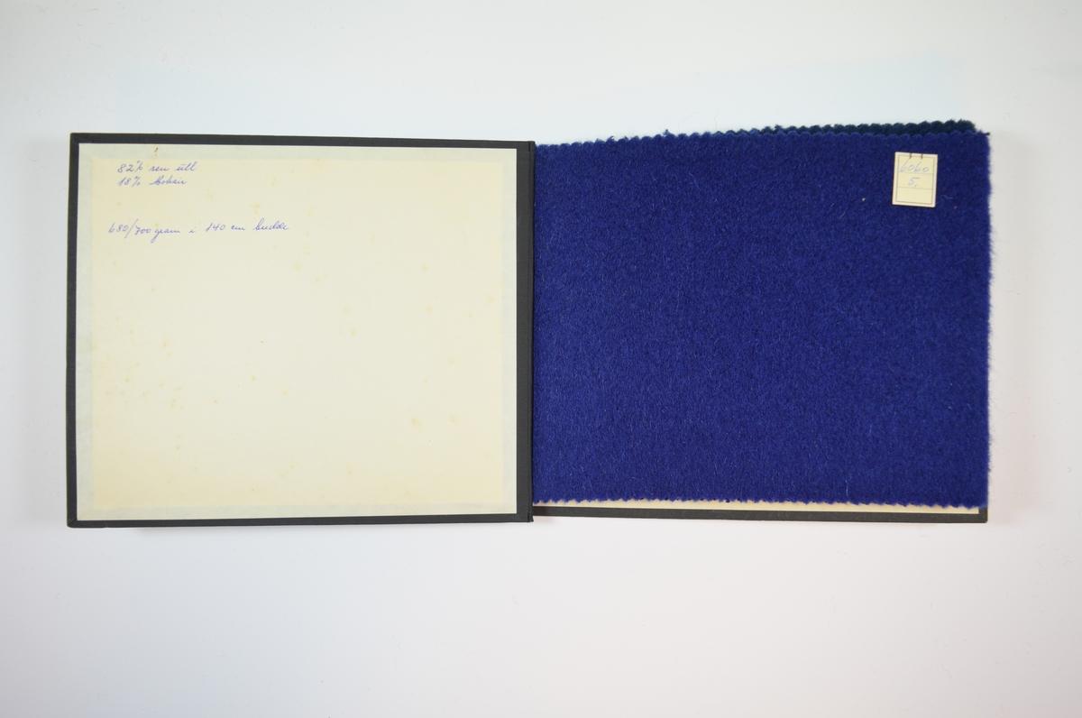 Rektangulær prøvebok med harde permer og tre stoffprøver. Permene er laget av hard kartong og er trukket med sort tynn tekstil. Boken inneholder tykke ensfargede ullstoff. Stoffene ligger brettet dobbelt i boken slik at vranga skjules. Tovet/valket. Stoffene er merket med en firkantet papirlapp, festet til stoffet med metallstifter, hvor nummer er påført for hånd.   Stoff nr. 6060/5, 6060/6, 6060/7.