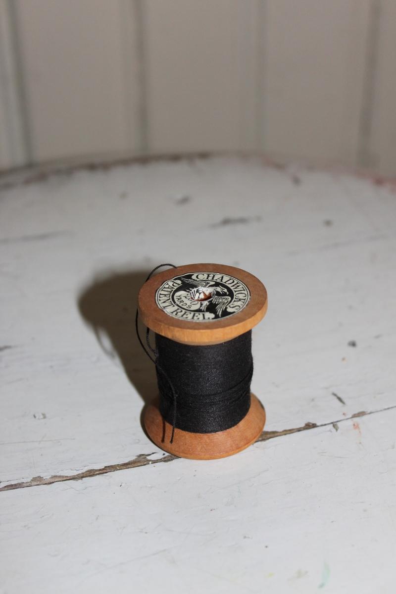 Trådrulle med svart tråd. Rulle i ofärgat trä med klisterlapp i botten och på ovansidan. Trådrullen avsedd att användas till symaskin.