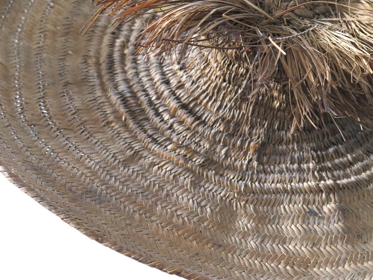 Vidbremmet hatt i mykt strå, brunt, med en liten sylindrisk  pull med  en 4,5 cm lang krans av strå rundt toppen. I toppen en sort  buet  fjær, gjennom pullen en hattenål i form av en fjærstilk.