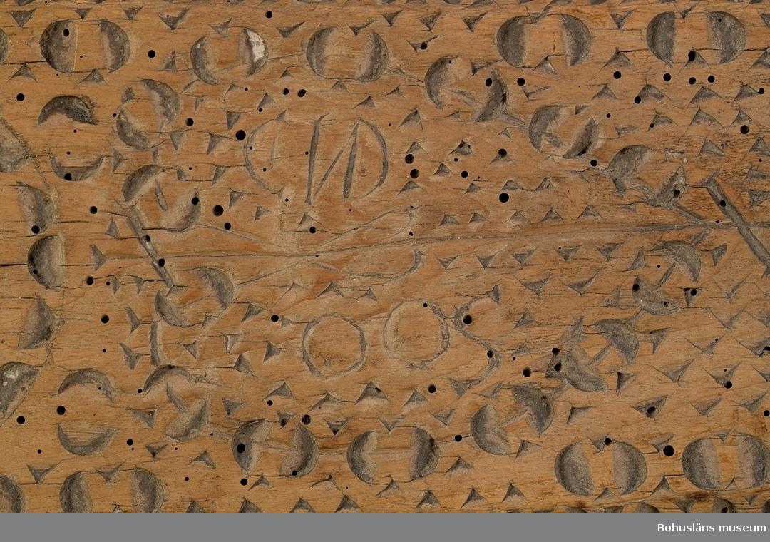 """Platt, rektangulärt redskap med stiliserat handtag i ett stycke. På ovansidan är den täckt med skuren dekor i bl.a karv- och nagelsnitt med bl.a tre rosetter i olika utförande. På mitten är ett stiliserat hjärta med ägarinitialerna """"CND"""" och """"OOS"""" i. Kanten är avfasad och på vardera sida handtaget är en hålkäl. Längs kanten är följande inskuret; """"BiURWiCK:DEN:7:NOWEMBER:1798: OOS:CND"""". Är en friargåva. Kavelrullen att linda tyget runt saknas. Skadedjursangrepp.  Litt.; Nylén, Anna-Maja, Hemslöjd, Håkan Ohlssons förlag, Lund, 1978, s. 359-363. Fredlund, Jane, Stora boken om livet förr, ICA-förlaget, Västerås, 1981, 40-49, 170-177. Sörensen, Steinar, Mangletreet-Glatteredskap og festegave, Glomdalsmuseets småskrifter nr. 3, Engers Boktryckeri A/S, Otta.  Ur handskrivna katalogen 1957-1958: Kavelbräde. CWD.OOS. dat. 1798 Mangelbräde L. 80 Br. 13,5 Trä med karvsnittsmönster och text. Föremålet helt. Maskhål.  Lappkatalog: 72"""