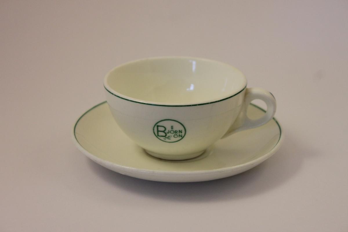 Kaffekopp och  fat i benporslin märkta med Björnön innefattat i en ring och med en bladranka. All dekor i grönt en grön rand pryder koppens och fatets kanter.