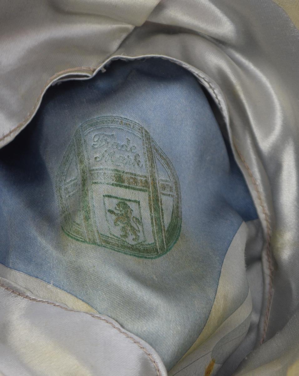 Rund pull, formet til for hånd, mørke blått ripsbånd med flat sløyfe, brem med svak oppbrettet kant bak og på sidene kantet med mørkeblått ripsbånd. Grått silkefor på sidene, glatt i pullen grå-blå sjatteringer. Engelsk firmamerke i gull og lys grønt produksjonsmerke i foret. Lys grå ca. 4 cm bred svetterem av skinn.