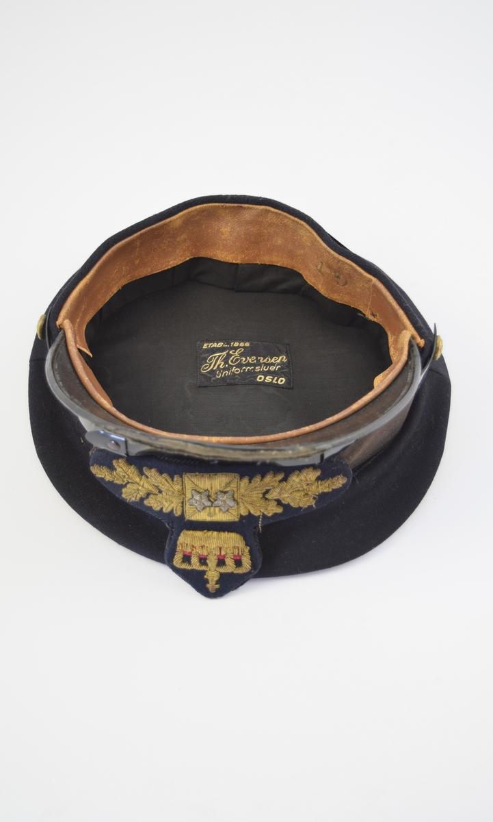 A) Uniformslue med brem fremme, lakkbånd over bremmen festet med to gullknapper med riksvåpnet på hver side. Strikkebånd med påsydd tøymerke dekorert blader, stjerner og krone av metalltråd. Flat pull. Svettebånd i lær på innsiden, merket med G.T  B) Uniformslue med brem fremme, lakkbånd over bremmen festet med to gullknapper med riksvåpnet på hver side. Strikkebånd med påsydd tøymerke dekorert blader, stjerne og krone av metall. Flat pull. Undersiden av bremmen har grønn farge.