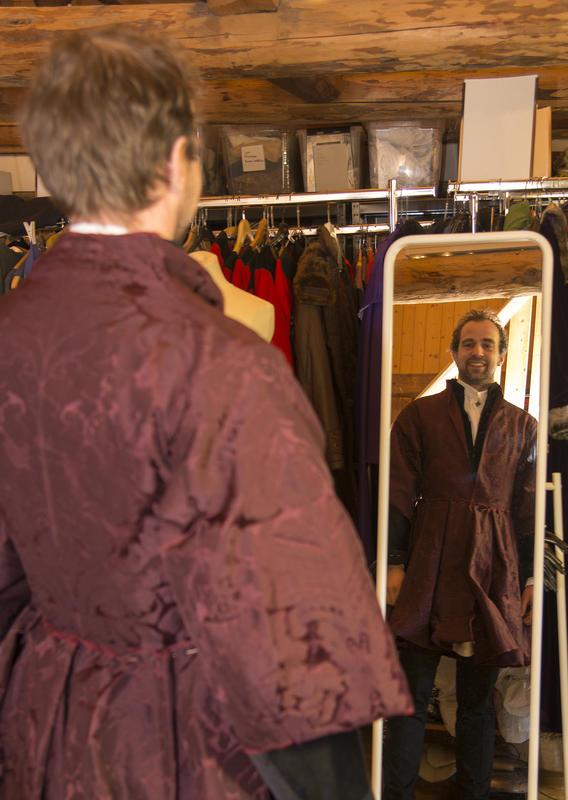 Mann i burgunderrød brokadejakke med store skjørt ser på seg selv i speilet og smiler. (Foto/Photo)