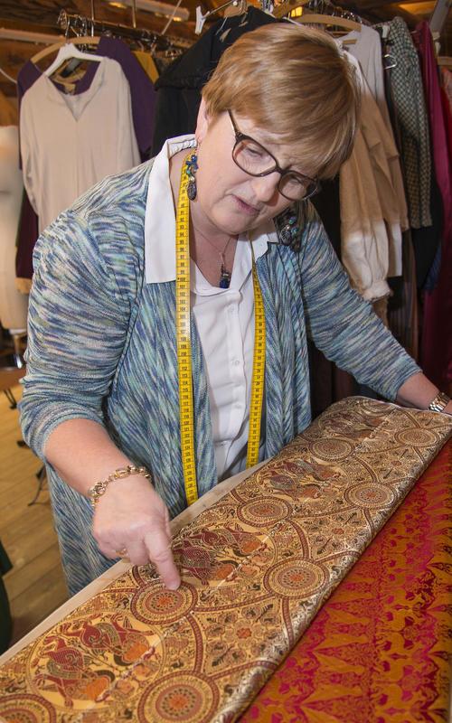 Skredderen viser fram en tøyrull med vakkert rødt og gyllent silkestoff med innfløkt mønster av blant annet arabiske tegn. (Foto/Photo)