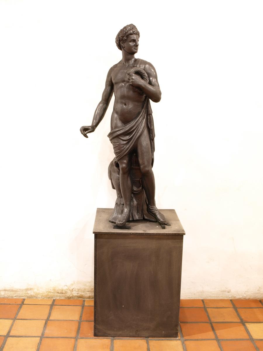 Statue av naken ung mann. Skulle hatt sverd i sin høyre hånd (mangler) og krans i sin venstre. Ved foten harnisk og hjelm. Figuren er støpt i 11 deler. Statuen stod på sokkel oppå ovnen.