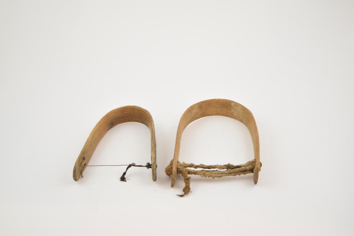 Kuklaver av en skåret tregrein som er bøyd til en u-form. Greina er helt flatskåret. I hver ende av to avlange hull ved siden av hverandre. Gjennom disse er det tredd en snor på tvers to ganger. .