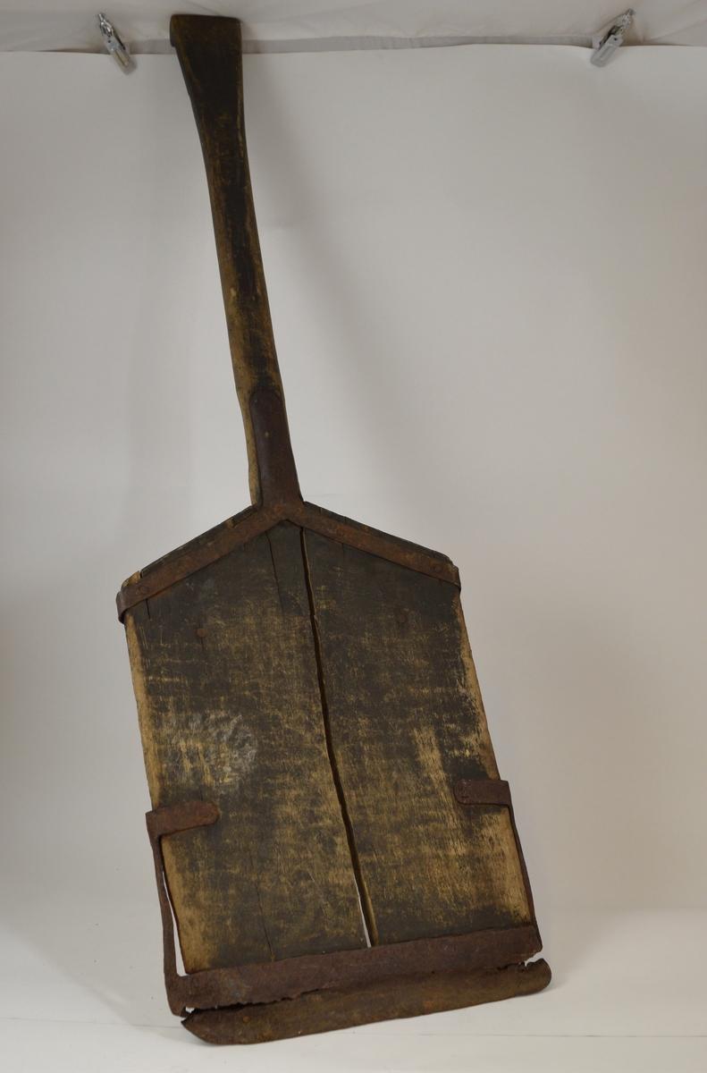 Snøskuffe av tre med metallbeslag. Rektangulært rett blad som skråner litt opp mot skaftet. Skaftet rett og firkantet, litt bredere og flatere i enden.